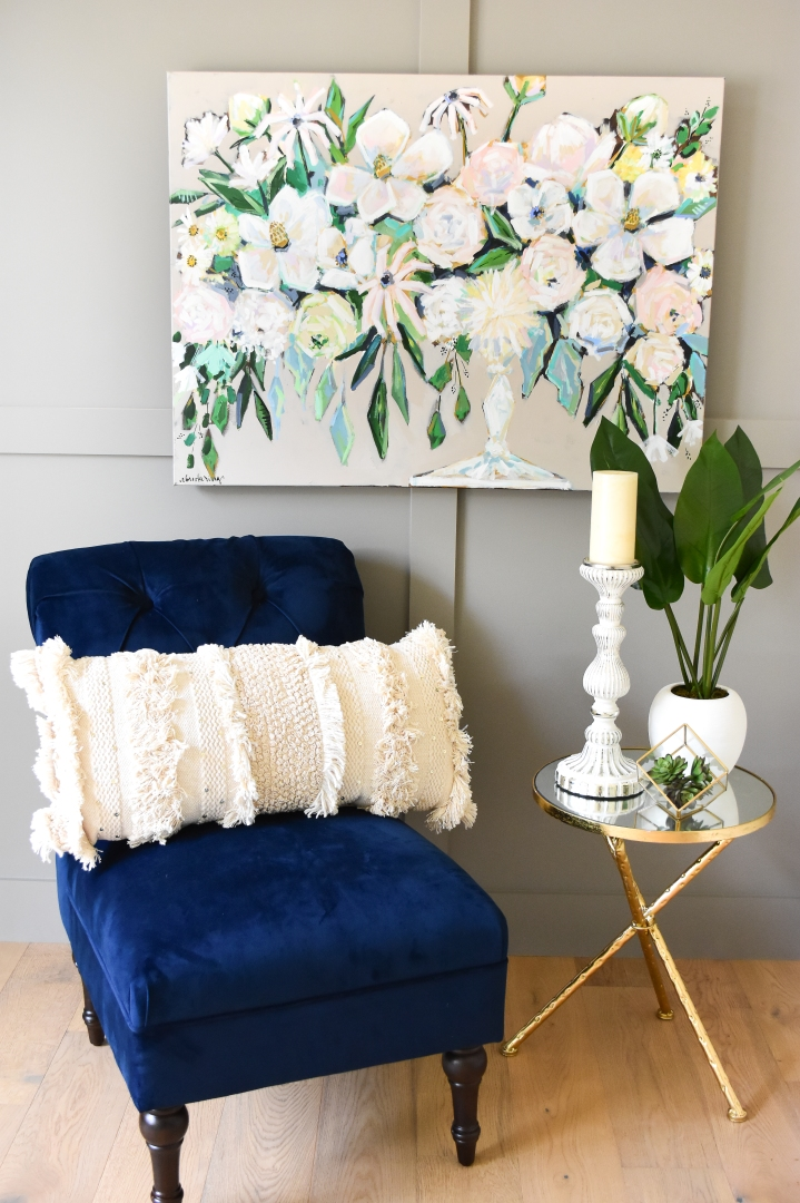 neutral floral painting paired with blue accent chair and gold side table.