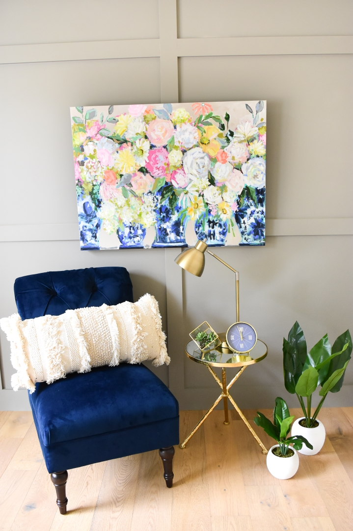 Bright floral painting in blue and white ginger jars with blue accent chair and gold side table.