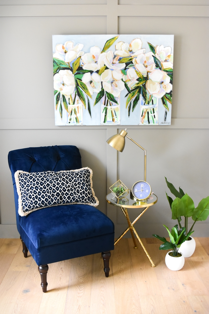 Magnolia painting styled next to blue velvet chair and cheetah print pillow