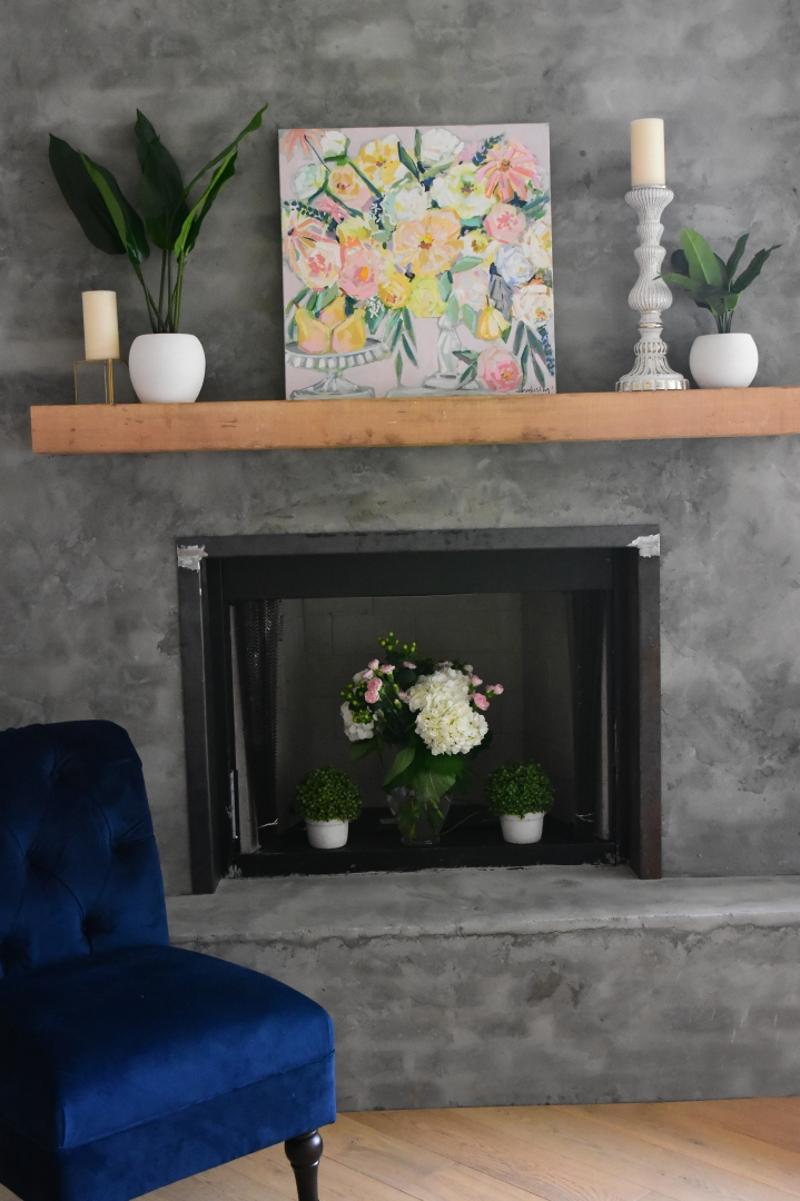 bright fruit and floral painting on modern fireplace paired with a blue accent chair.