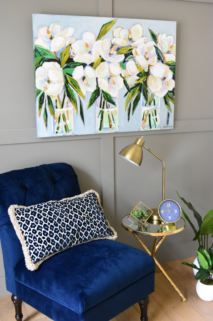 magnolia painting styled with blue background styled with blue velvet chair and gold side table.