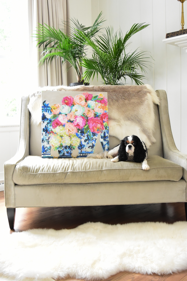 floral painting in blue and white ginger jars on couch with dog