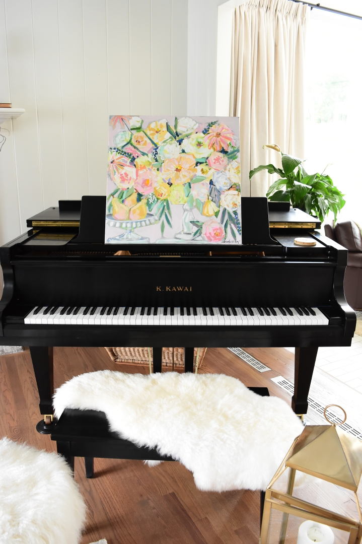 floral painting on piano with pears and white fur rug