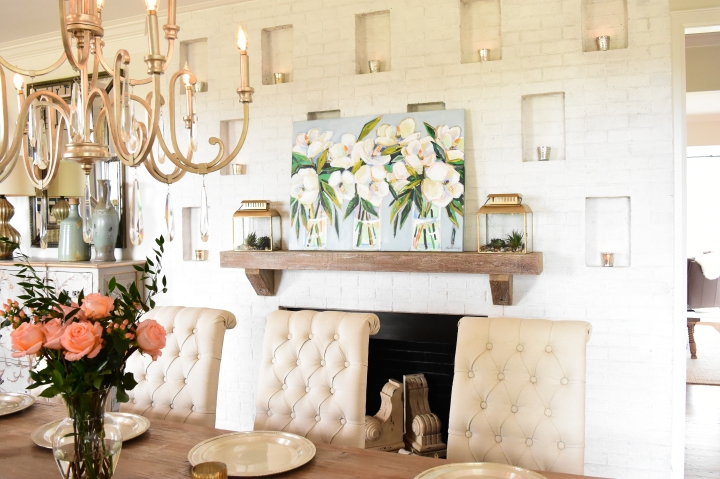 floral painting on mantle with gold chandelier and tufted chairs